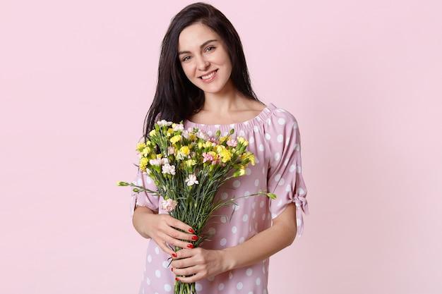Zadowolona dobrze wyglądająca młoda europejska kobieta z łagodnym uśmiechem, nosi sukienkę w groszki, trzyma bukiet kwiatów, chętnie odbiera od męża, modelki w różowym pastelowym kolorze.