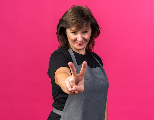 Zadowolona dorosła kaukaska fryzjerka w mundurze gestykuluje znak zwycięstwa na białym tle na różowym tle z miejscem na kopię