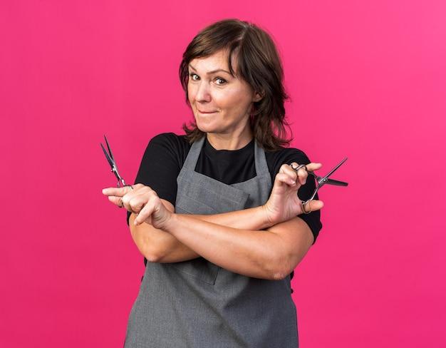 Zadowolona dorosła kaukaska fryzjerka w mundurze trzymająca nożyczki i patrząca na kamerę odizolowaną na różowym tle z miejscem na kopię