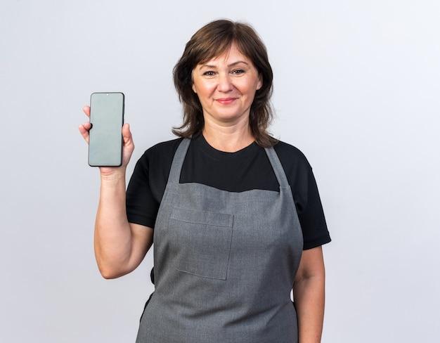 Zadowolona dorosła kaukaska fryzjerka w mundurze trzymająca telefon na białym tle z miejscem na kopię copy