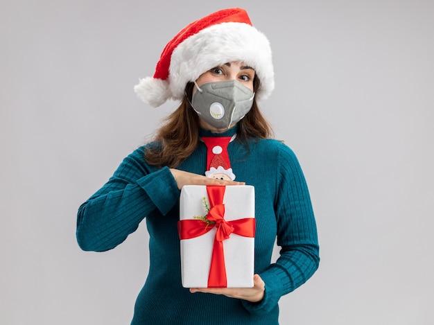 Zadowolona dorosła kaukaska kobieta w kapeluszu świętego mikołaja i krawacie świętego mikołaja w masce medycznej, trzymająca pudełko na prezent świąteczny na białym tle na białej ścianie z miejscem na kopię