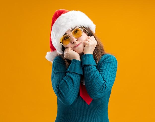 Zadowolona dorosła kaukaska kobieta w okularach przeciwsłonecznych z czapką i krawatem mikołaja kładzie pięści na twarzy na białym tle na pomarańczowym tle z miejsca na kopię
