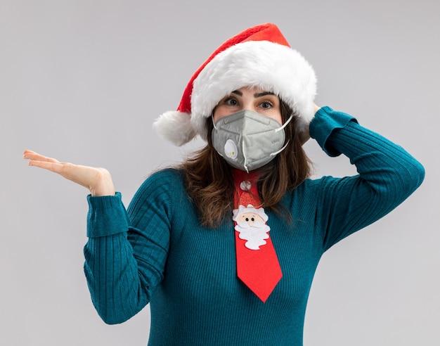 Zadowolona dorosła kaukaska kobieta z czapką mikołaja i krawatem świętego mikołaja w masce medycznej kładzie rękę na głowie i trzyma dłoń otwartą na białym tle z miejscem na kopię