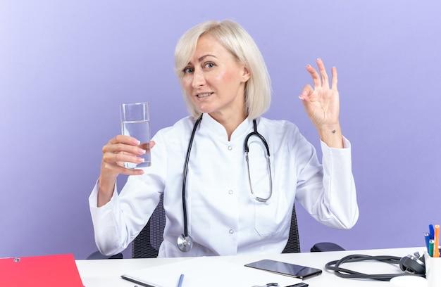 Zadowolona dorosła lekarka w szacie medycznej ze stetoskopem siedząca przy biurku z narzędziami biurowymi trzymająca szklankę wody i wskazująca znak ok na fioletowej ścianie z kopią miejsca