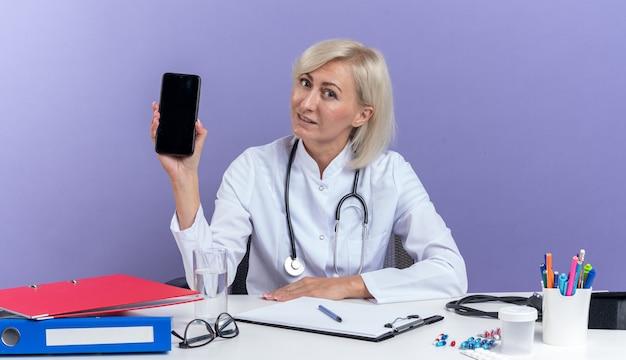 Zadowolona dorosła słowiańska lekarka w szacie medycznej ze stetoskopem siedzi przy biurku z narzędziami biurowymi trzymając telefon na białym tle na fioletowym tle z kopią przestrzeni