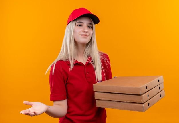 Zadowolona dostawa młoda dziewczyna ubrana w czerwoną koszulkę i czapkę, trzymając pudełko po pizzy, trzymając rękę w aparacie na na białym tle pomarańczowy