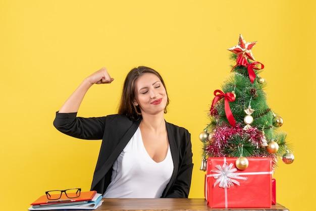 Zadowolona dumna młoda kobieta w garniturze w pobliżu udekorowanej choinki w biurze na żółto