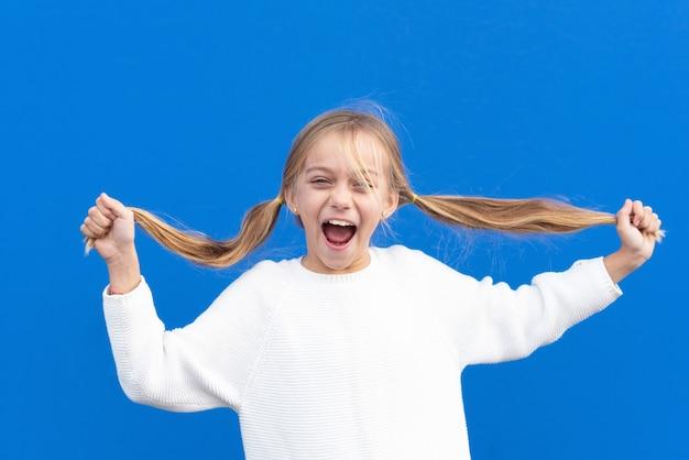 Zadowolona dziewczyna trzymając warkocze i śmiejąc się