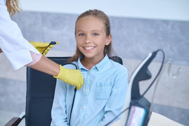 Zadowolona dziewczyna uśmiecha się do kamery przed badaniem słuchu