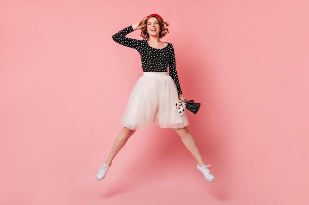 Zadowolona dziewczyna w białej spódnicy skacze z uśmiechem. pełny widok długości kręcone kobiety zabawy na różowym tle.