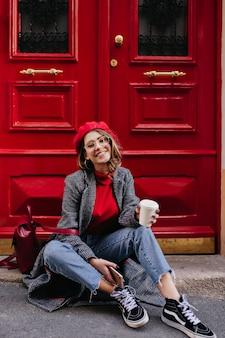 Zadowolona dziewczyna w okularach i czarnych gumowych butach pije kawę, siedząc w pobliżu czerwonych drzwi