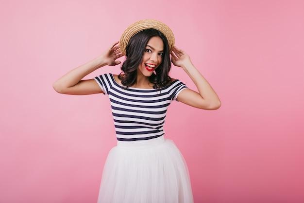 Zadowolona dziewczyna w t-shirt w paski z wyrazem śmiesznej twarzy. wewnątrz portret wesoły kaukaski kobieta z brązowymi włosami taniec.