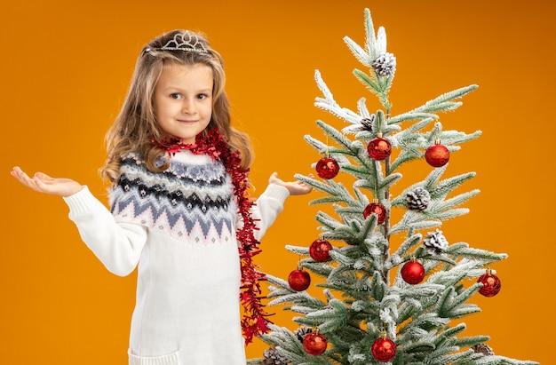 Zadowolona dziewczynka stojąca w pobliżu choinki ubrana w tiarę z girlandą na szyi, rozkładająca ręce na białym tle na pomarańczowym tle
