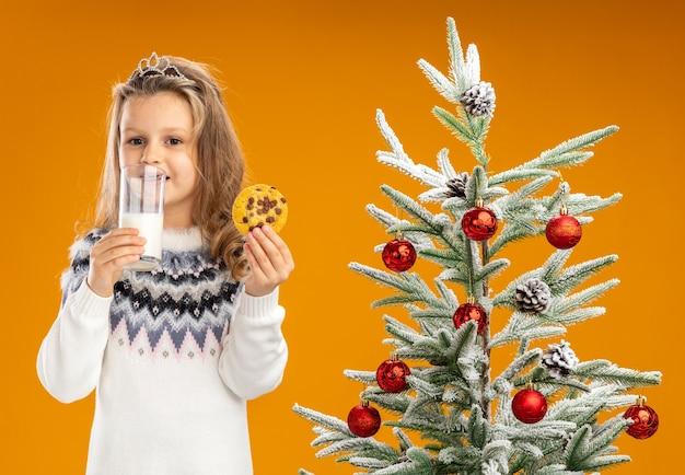 Zadowolona dziewczynka stojąca w pobliżu choinki ubrana w tiarę z girlandą na szyi, trzymając szklankę mleka z ciasteczkami na białym tle na pomarańczowym tle