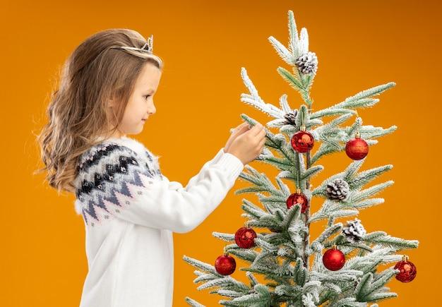 Zadowolona dziewczynka stojąca w pobliżu choinki ubrana w tiarę z girlandą na szyi trzymająca drzewo na białym tle na pomarańczowym tle