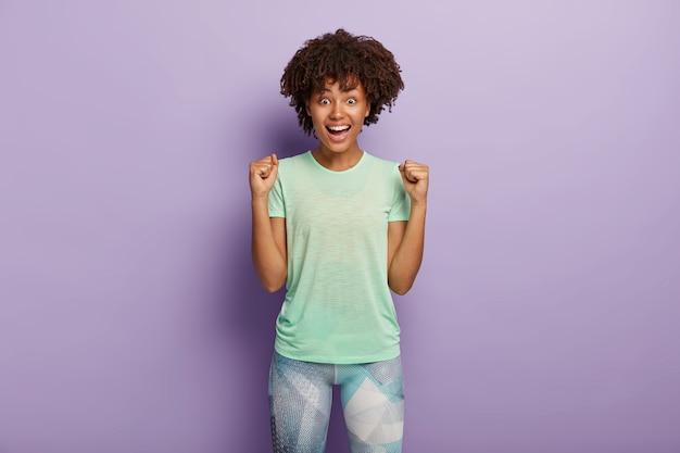 Zadowolona energiczna kobieta zaciska pięści, ogląda mecz piłki nożnej, będąc wielką fanką, ubrana w aktywny strój