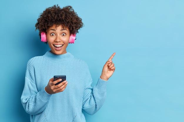 Zadowolona etniczna kobieta z włosami afro wskazuje, że w prawym górnym rogu trzyma nowoczesną komórkę słuchającą muzyki przez słuchawki stereo ubrane w luźny sweter z dzianiny
