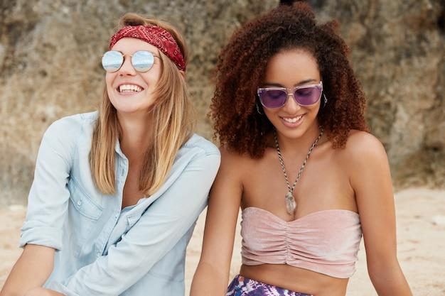 Zadowolona europejka w modnych odcieniach, nosi opaskę, patrzy na jasne słońce na niebie, siedzi obok swojej afroamerykańskiej przyjaciółki, ma prawdziwą przyjaźń, siedzi na klifie lub górze