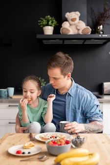 Zadowolona głodna córeczka siedzi na kolanach ojca i je naleśniki wykonane przez ostrożnego ojca, ojca i córkę jedzących razem śniadanie