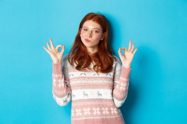 Zadowolona i dumna ruda dziewczyna kiwa głową z aprobatą, pokazując znak porządku, nie zły lub gest pochwalny, stojąc na niebieskim tle