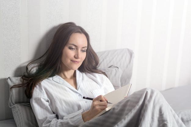 Zadowolona i szczęśliwa uśmiechnięta dziewczyna leżąca na łóżku w pokoju i pisze dziennik swoich marzeń, planów, celów, doświadczeń, pomysłów, przeżywanych emocji i uczuć