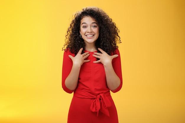 Zadowolona i wdzięczna delikatna delikatna kędzierzawa dziewczyna w czerwonej sukience przyciskająca dłonie do piersi, zaskoczona niespodziewanym delikatnym, serdecznym prezentem dziękująca uśmiechnięta zachwycona na żółtym tle