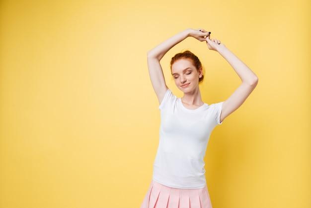 Zadowolona imbirowa dziewczyna pozuje z ręką nad głową i zamkniętymi oczami