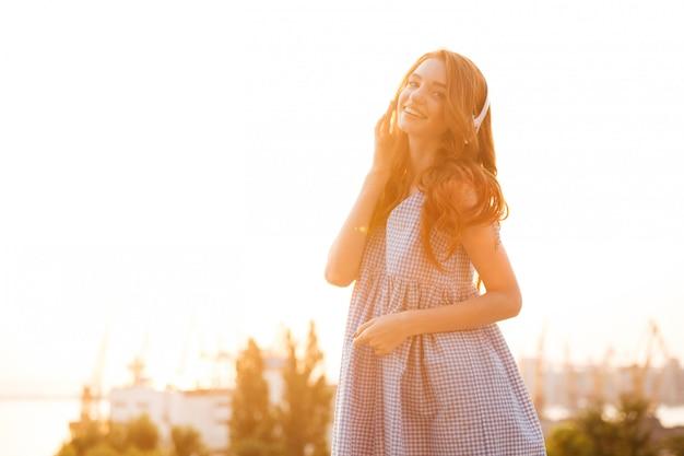 Zadowolona imbirowa kobieta w sukni słucha muzyki