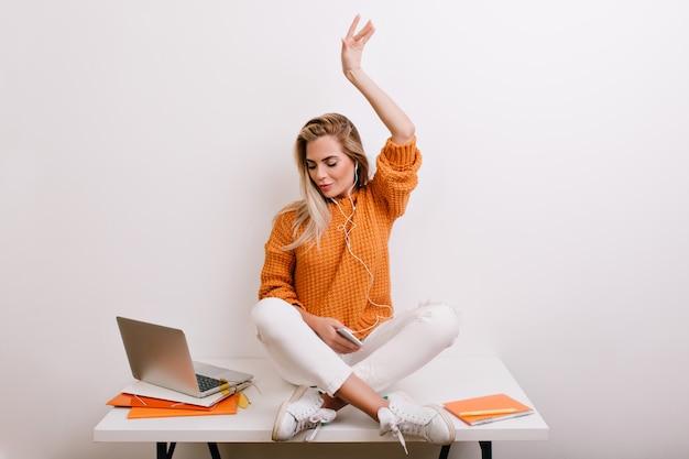 Zadowolona jasnowłosa kobieta w modnych butach sportowych, słuchająca muzyki w słuchawkach i patrząc na ekran laptopa