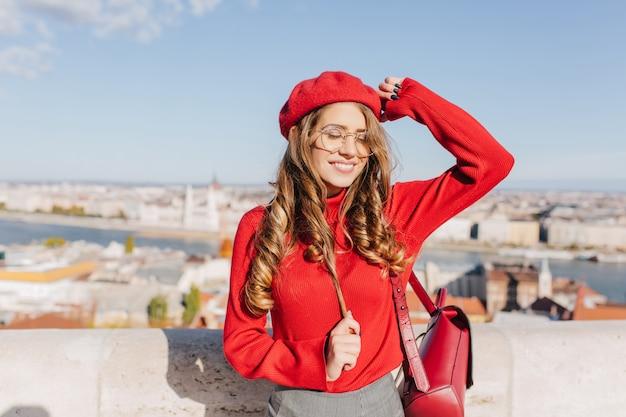 Zadowolona kaukaska dziewczyna bawi się brązowymi włosami w słoneczny dzień w europejskiej stolicy