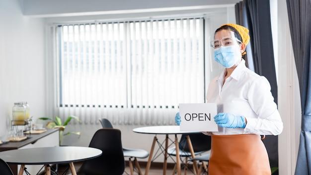 Zadowolona kelnerka z ochronną maską na twarzy trzyma otwarty znak do ponownego otwarcia w swojej restauracji po zamknięciu
