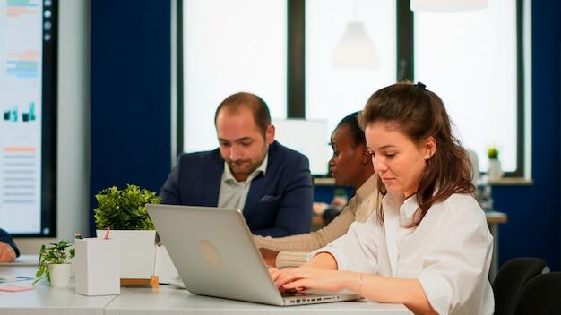 Zadowolona kobieta biznesu odpowiadająca na e-maile piszące na laptopie uśmiechnięta siedząca przy biurku w zajętym biurze startowym, podczas gdy zróżnicowany zespół analizuje dane statystyczne. wieloetniczny zespół pracujący nad nowym projektem