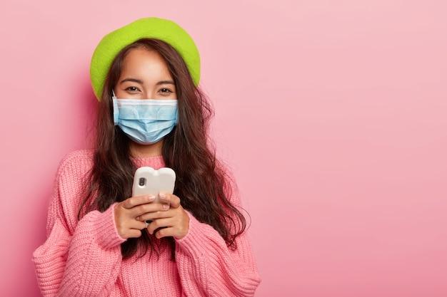 Zadowolona kobieta ma grypę, nosi ochronną maskę medyczną, aby nie zarażać innych ludzi, używa telefonu komórkowego do surfowania po internecie, czyta, jak leczyć choroby w internecie, ubrana w modne ubrania