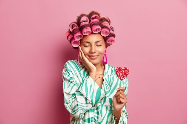 Zadowolona kobieta ma zamknięte oczy cieszy się domową atmosferą sprawia, że fryzura nakłada wałki do włosów trzyma smaczne cukierki nosi szlafrok izolowany na różowej ścianie