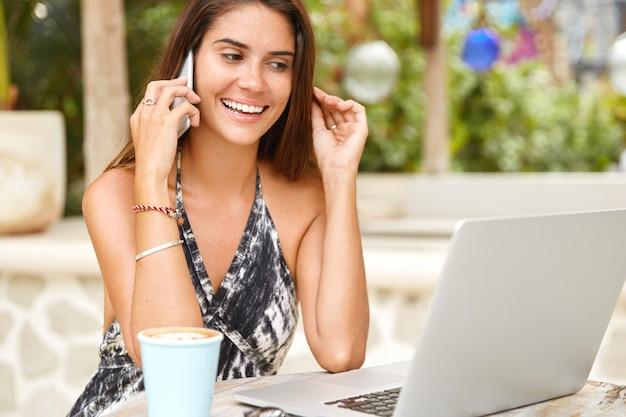 Zadowolona kobieta o radosnym wyrazie twarzy, ma atrakcyjny wygląd, rozmawia na smartfonie z kolegą lub partnerem, wykorzystuje nowoczesne technologie do pracy i komunikacji. atrakcyjna kobieta rozmowy.