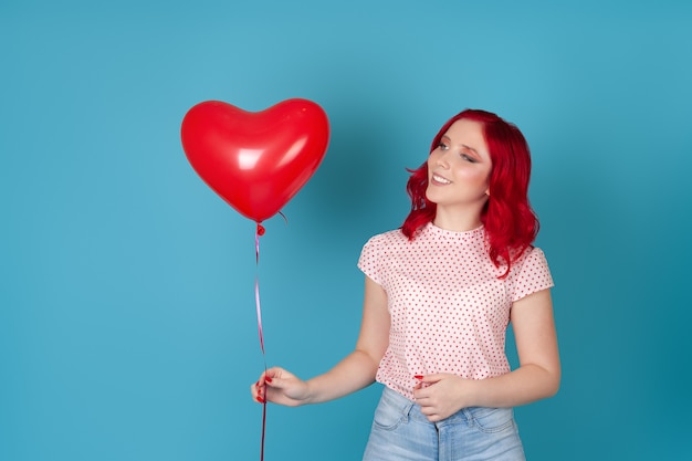 Zadowolona kobieta o rudych włosach patrząc na czerwony latający balon w kształcie serca