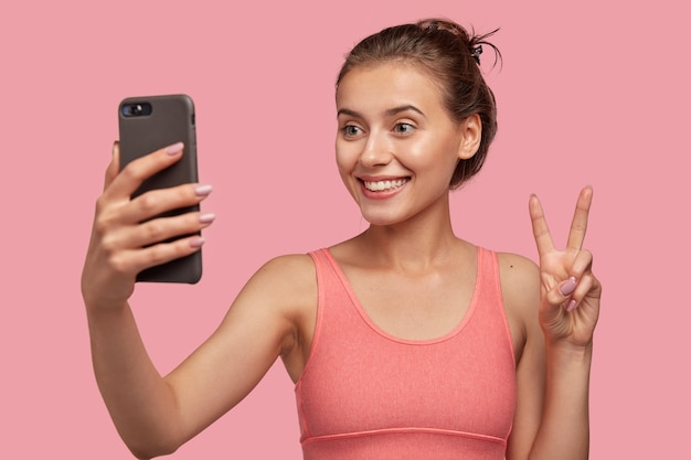 Zadowolona kobieta o zębowatym uśmiechu, uczesanych włosach, wysportowanej sylwetce, robi znak pokoju lub gest v z telefonu komórkowego, pozuje do selfie, odizolowana na różowej ścianie. wideo rozmowa