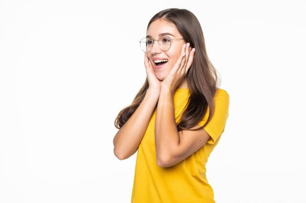 Zadowolona kobieta opiera się na dłoniach i patrzy w kamerę na białej ścianie