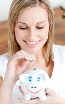 Zadowolona kobieta oszczędzania pieniędzy w piggy-bank
