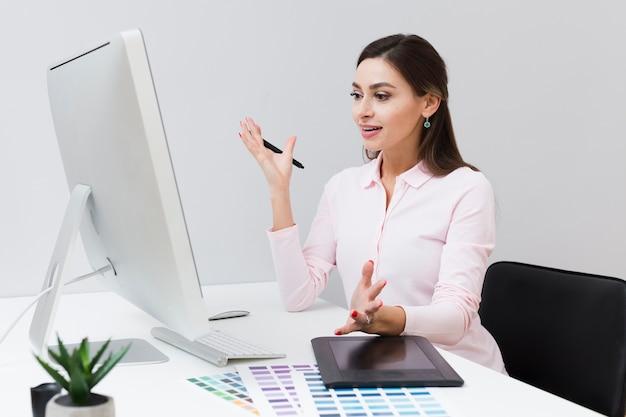 Zadowolona kobieta patrzeje komputer podczas gdy przy pracą