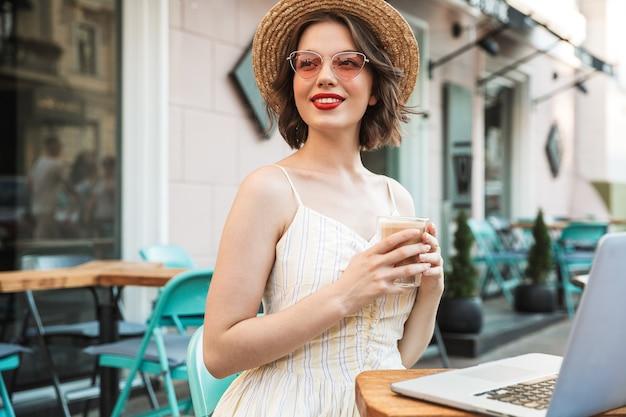 Zadowolona kobieta pije kawę w sukience i słomkowym kapeluszu