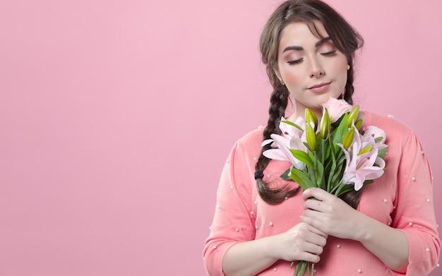 Zadowolona kobieta pozuje podczas gdy trzymający bukiet leluje w rękach