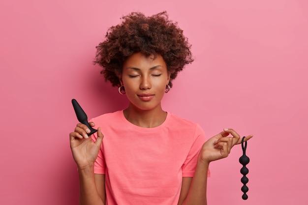Zadowolona kobieta pozuje z koralikami analnymi, korkiem analnym używanym do kulminacji, dla przyjemnych odczuć w odbycie, osiąga przyjemność seksualną za pomocą zabawek erotycznych. erotyczna stymulacja skupiona na odbycie i odbytnicy