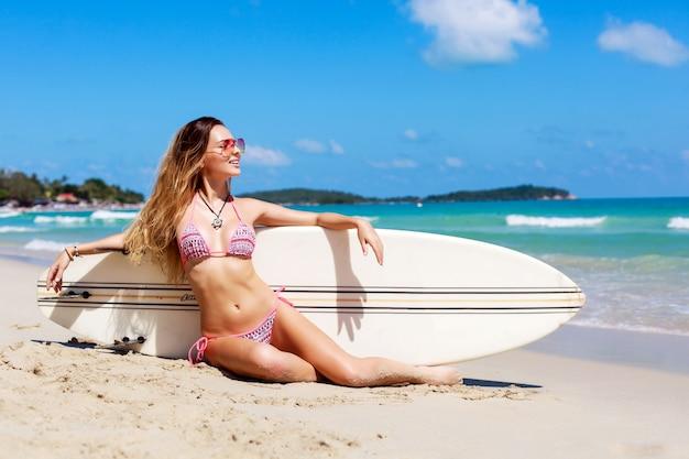 Zadowolona kobieta siedzi na piasku z jej deska surfingowa