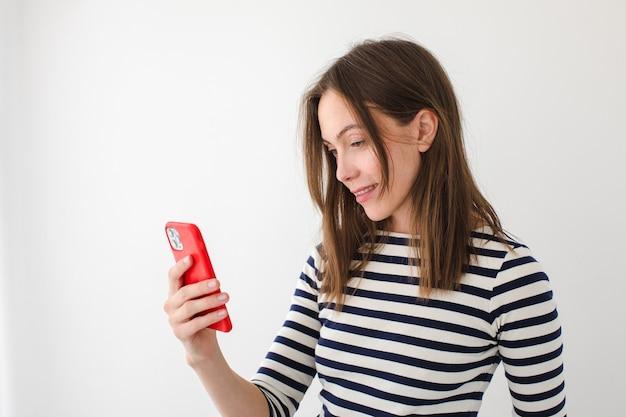 Zadowolona kobieta stojąca w nowoczesnym mieszkaniu i czytająca wiadomości na telefonie komórkowym, bawiąc się w weekend