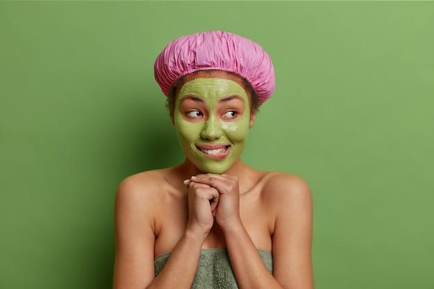 Zadowolona kobieta trzyma ręce pod brodą, radośnie patrzy na bok, nosi wodoodporny kapelusz ręcznik wokół nagiego ciała, odwraca wzrok z wesołym wyrazem twarzy odizolowanym od zielonej ściany