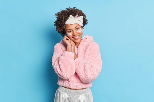 Zadowolona kobieta trzyma ręce w pobliżu twarzy, uśmiecha się delikatnie, nosi opaskę na oczach, a piżama nakłada kolagenowe łaty odizolowane na niebieskiej ścianie