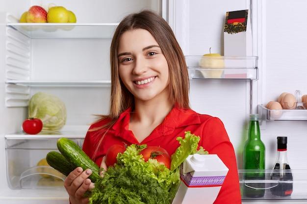 Zadowolona kobieta trzyma świeże warzywa i mleko
