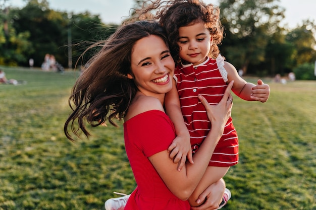 Zadowolona kobieta trzymając córkę i śmiejąc się do kamery. plenerowe zdjęcie emocjonalnej młodej mamy relaksującej się w weekend z dzieckiem.