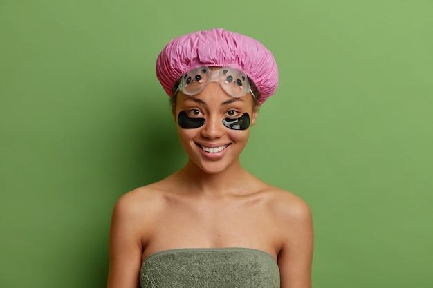 Zadowolona kobieta uśmiecha się delikatnie nakłada hydrożelowe plastry pod oczy, aby zredukować zmarszczki, a drobne linie odświeżyły skórę po wzięciu prysznica odizolowanego od zielonej ściany